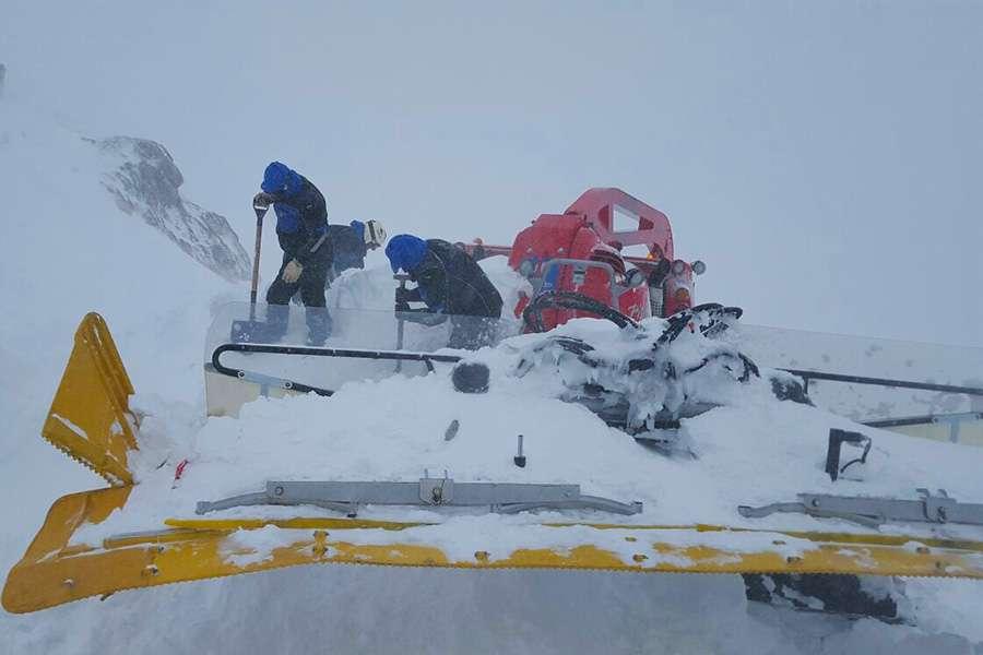 rabajadores de la estación tratan de liberar la máquina sepultada por la nieve.